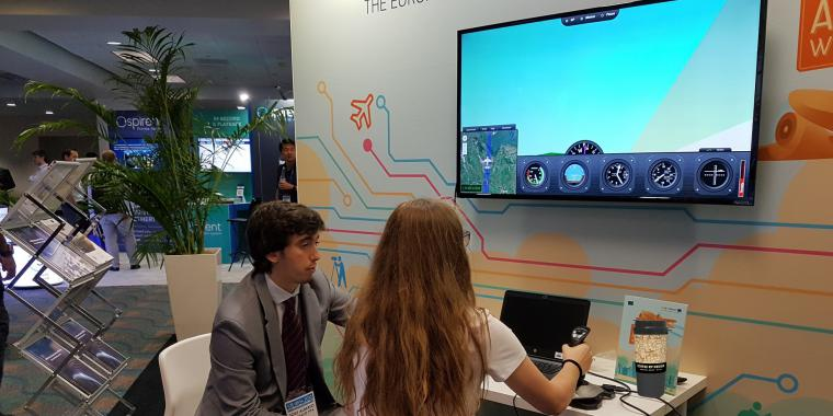 Two visitors using Web-based flight simulator at ION GNSS+